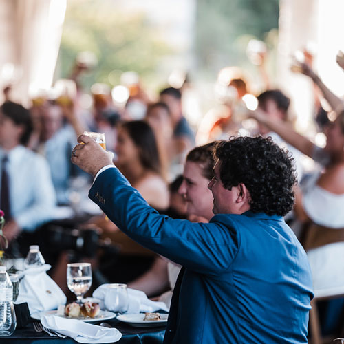 Guests toast at tented beach wedding venue.