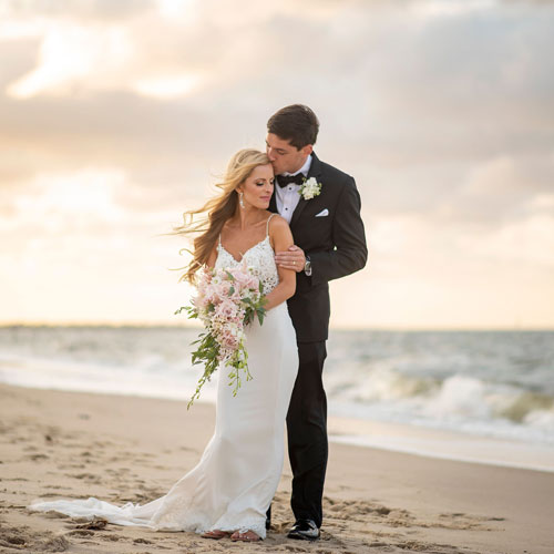Bride and groom at beach wedding venue at sunset.