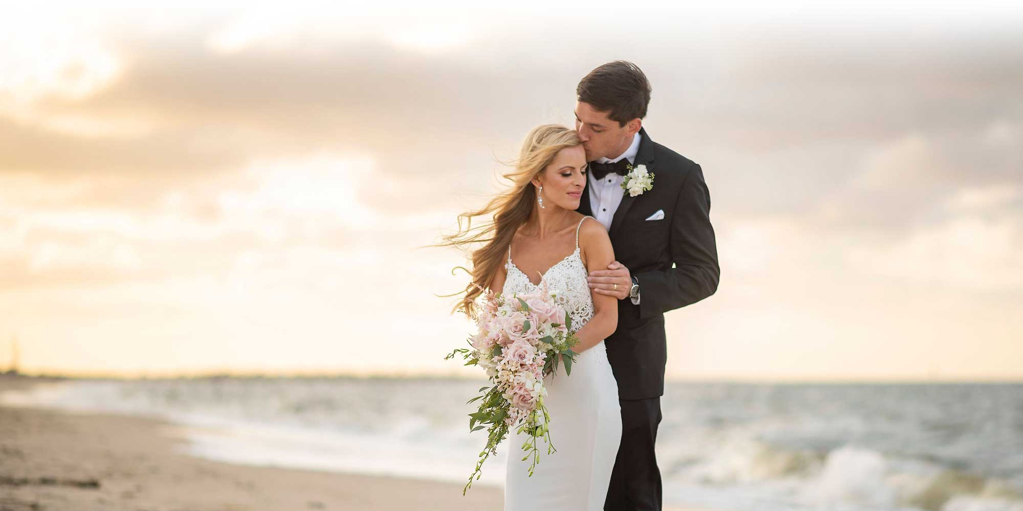 Bride and groom embrace at beach wedding venue at sunset.