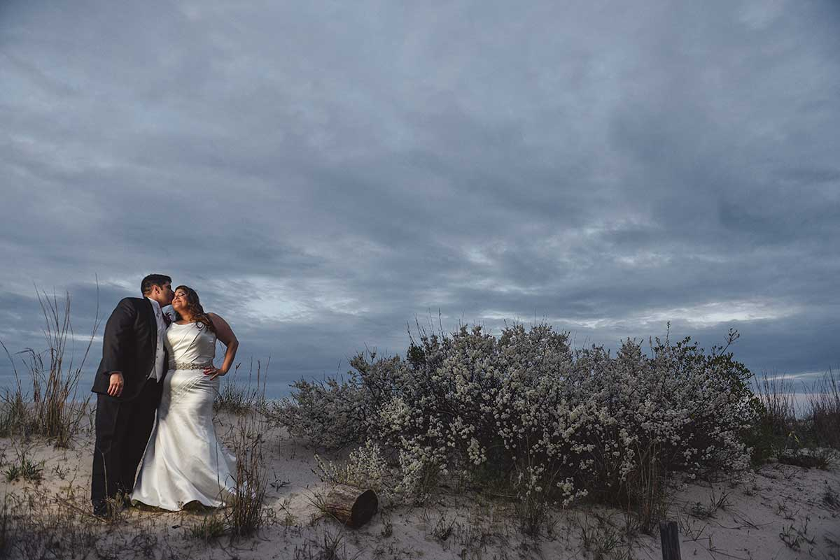 Bride and groom on beach dune next to blooming bayberry bush.