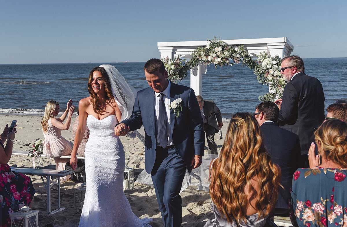 Bride and groom walking down the aisle at Delaware beach wedding.