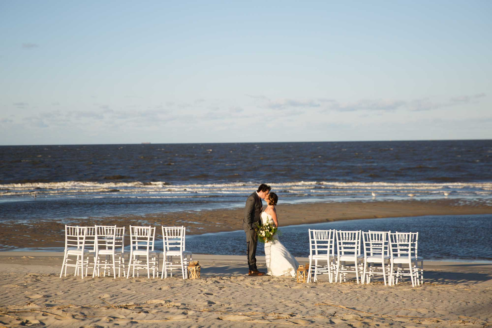 Bride and groom kiss on beach at wedding venue.